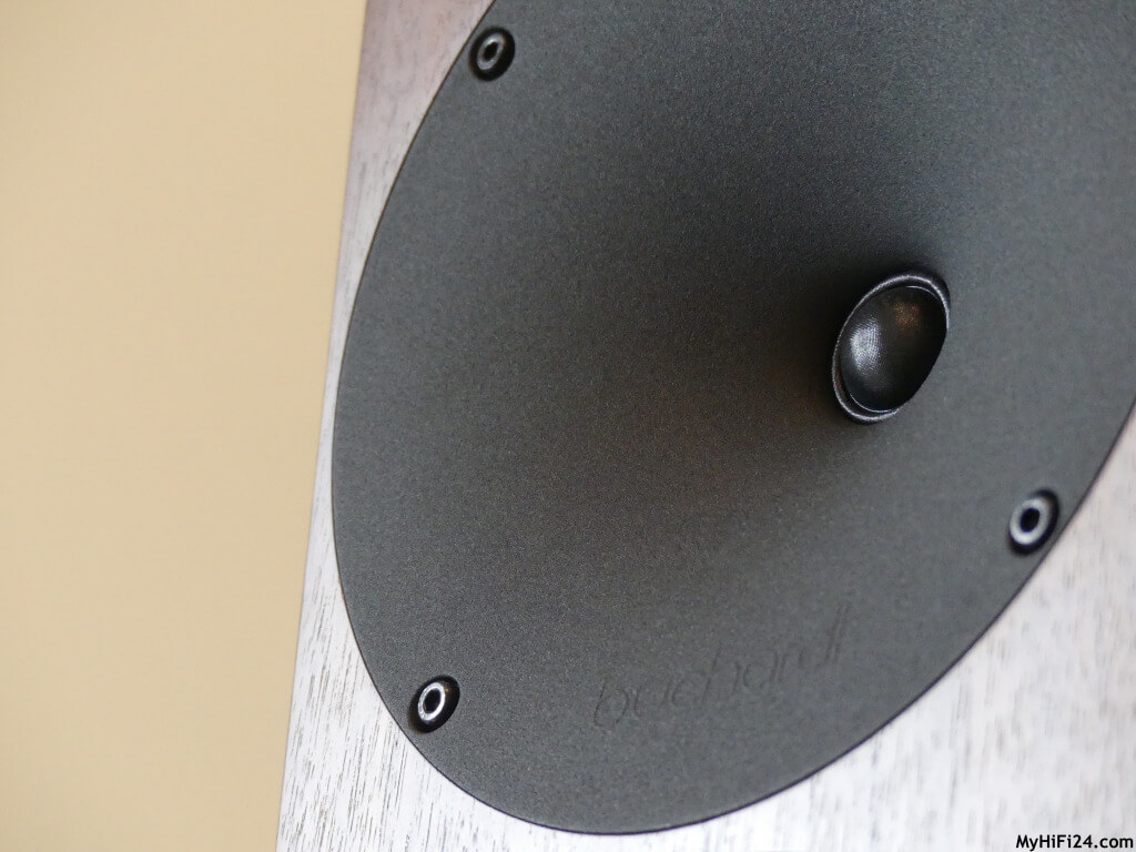 Wir haben hier einen 2,5-Wege-Aktivlautsprecher, der durch die variablen Klangpresets zu einem 3-Wege-Aktivlautsprecher konfiguriert werden kann. Er hat drei Endstufen pro Lautsprecher, die jeweils 150 Watt mit sich bringen. Als Hochtöner kommt ein spezial gewebtes Textil mit CDC-Wellenleiter aus Aluminium mit 19 mm in Spiel. Beim Mitteltöner wird auf ein 150 mm Langhubchassis gesetzt sowie beim Tieftöner, der sich aber auf der Rückseite des Lautsprechers befindet. Vorteil hierbei ist, dass der Aktivlautsprecher einen knackigen Bass in den Raum hinein zaubert. Das Gehäuse ist hochwertig verarbeitet sowie die eingesetzten Chassis. Der Aktivlautsprecher bringt eine Höhe von 365 mm, eine Breite von 180 mm und eine Tiefe von 280 mm gem. Herstellerangaben mit. Pro Lautsprecher haben wir ungefähr ein Gewicht von 12,5 kg.